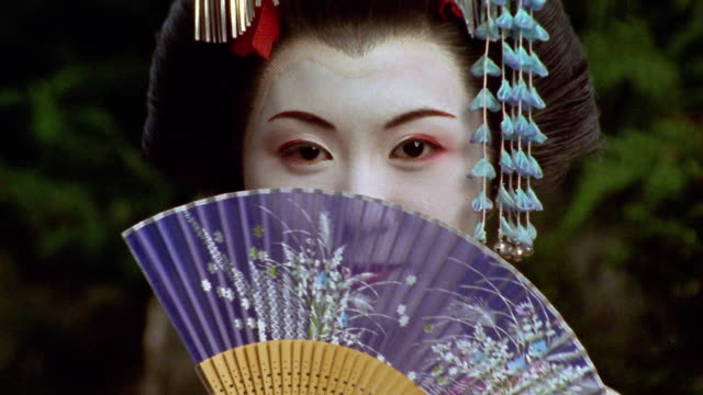 Close up Japanese woman in geisha makeup and costume moving fan across face / Japan