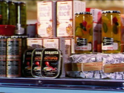 1962 close up PAN jars, cans + boxes of gourmet food on grocery store shelf / industrial