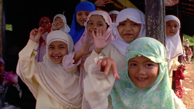 close up pan javanese children in native dress waving at camera outdoors / java, indonesia - indonesian ethnicity stock videos & royalty-free footage