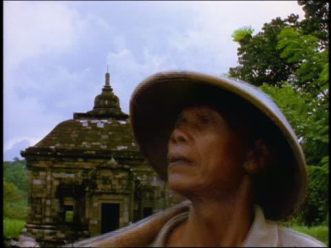 vidéos et rushes de portrait close up javanese man with hat rising in front of temple / central java, indonesia - seulement des hommes d'âge mûr