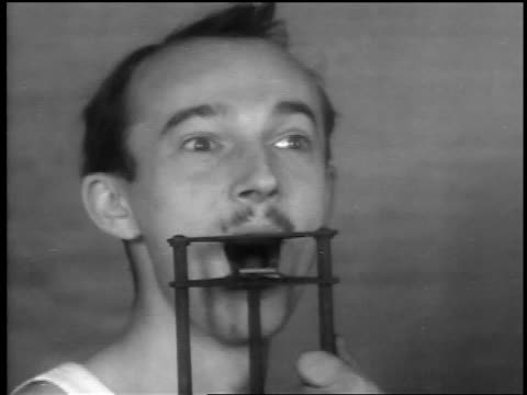 b/w 1932 close up jaw-breaking torture device being demonstrated on man - torture stock videos & royalty-free footage