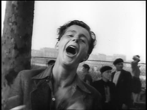 B/W 1944 close up jubilant Frenchman shouting for joy at camera at Liberation of Paris / documentary
