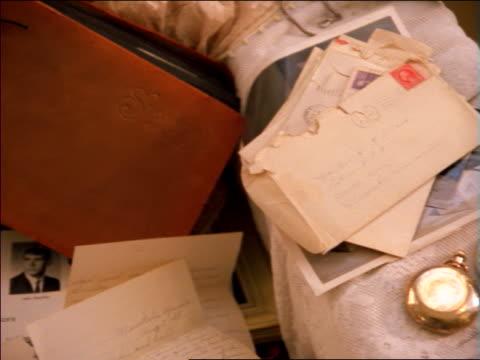 vidéos et rushes de close up pan keepsakes in trunk including letter, photos, yearbook and benny goodman album - nostalgie