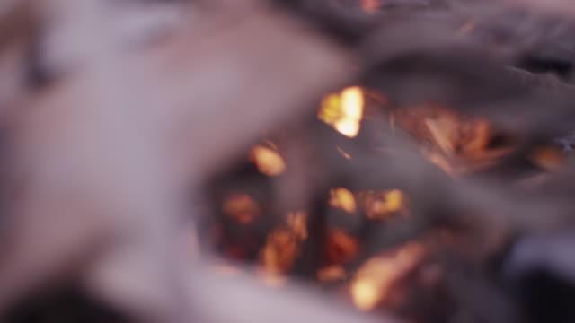 Close up, kindling begins to burn in campfire