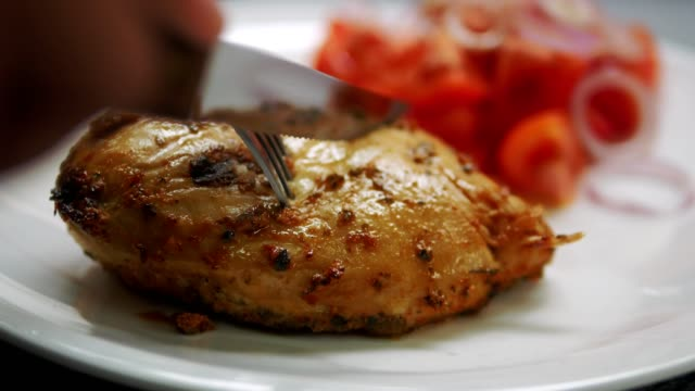 vídeos de stock e filmes b-roll de close up knife cutting chicken steak on white plate - cortado em filete