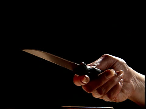 Close up knife laying on table/ hand picking up knife, as person examines it/ hand putting down knife/ picking knife up