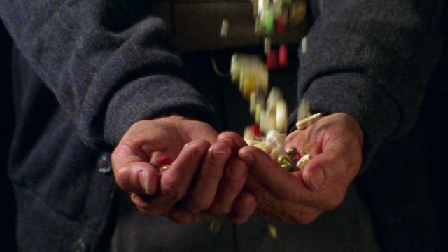 close up large amount of pills falling into senior man's cupped hands