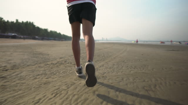 close up leg of man jogging on beach in the morning - one young man only stock videos & royalty-free footage