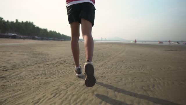 vídeos y material grabado en eventos de stock de cerca de la pierna del hombre corriendo en la playa por la mañana - un solo hombre joven
