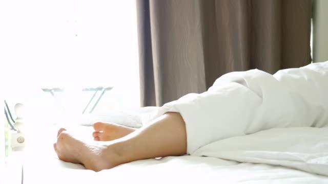 朝寝室のベッドで目を覚ます女性の脚をクローズアップ - シーツ点の映像素材/bロール