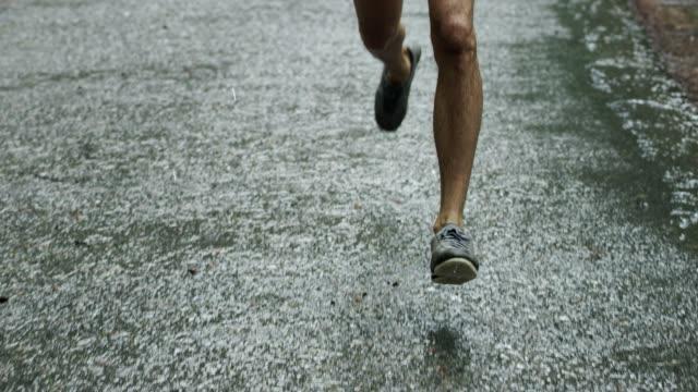vidéos et rushes de fermez-vous vers le haut du projectile de jambe d'un jogging sportif de jeune homme - chaussures