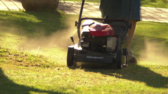 close up legs of anon man wearing shorts and sandshoes as mows front lawn using masport mower - back and forth / man cleans out boat parked on... - tagliaerba video stock e b–roll
