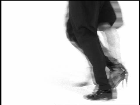 b/w overexposed close up legs of couple tango dancing on white surface in studio - tangoing stock videos & royalty-free footage