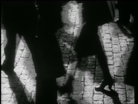 b/w 1939 close up legs of crowd walking on cobblestone street / nyc / documentary - cobblestone stock videos & royalty-free footage