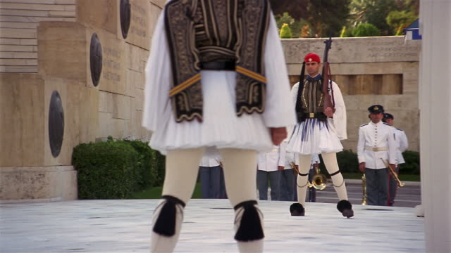vidéos et rushes de close up legs of evzone (greek guard) / zoom out changing of the guard ceremony outside parliament / athens - athènes