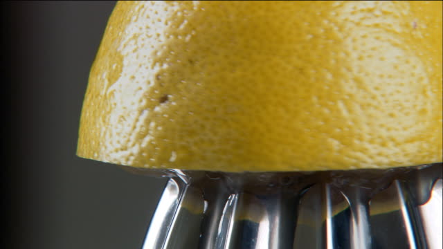 close up lemon being squeezed on citrus juicer - citrus fruit stock videos & royalty-free footage