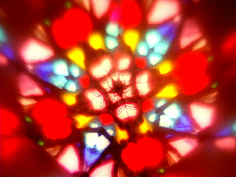 stockvideo's en b-roll-footage met close up light filtering through colorful kaleidoscope as pattern changes - psychedelisch