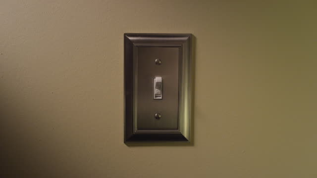 close up light switch on a wall - man's hand enters frame and turns light on and then off. - light switch stock videos & royalty-free footage
