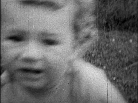 movie close up lindbergh baby crawling on grass outdoors / sequence - 1931年点の映像素材/bロール