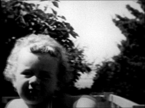 movie close up lindbergh baby sitting in crib outdoors playing - anno 1931 video stock e b–roll
