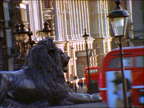 close up lion on fountain in Trafalgar Square / double decker buses on Whitehall Street in background / London