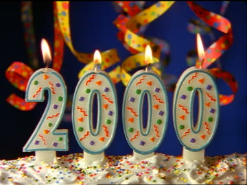 stockvideo's en b-roll-footage met close up lit year 2000 candles with streamers + confetti falling in background - 1999