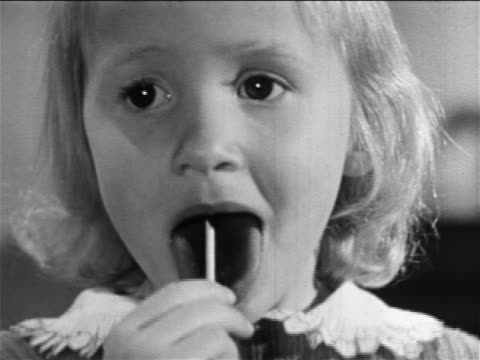 B/W 1957 close up little blond girl licking lollipop / educational