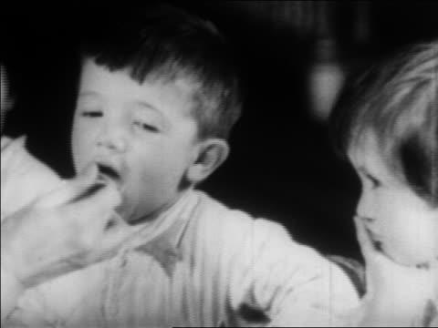 stockvideo's en b-roll-footage met b/w 1934 close up little boy being served spoonful of medicine at nursery school / wpa project / newsreel - drinking health 1930 film