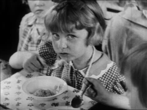 b/w 1934 close up little girl eating in nursery school / wpa project / newsreel - anno 1934 video stock e b–roll