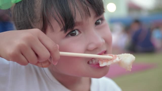 close up little girl eating japanese sushi roll with chopsticks. - sushi stock videos & royalty-free footage