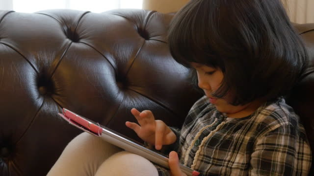 close up little girl using tablet on sofa - 集中点の映像素材/bロール