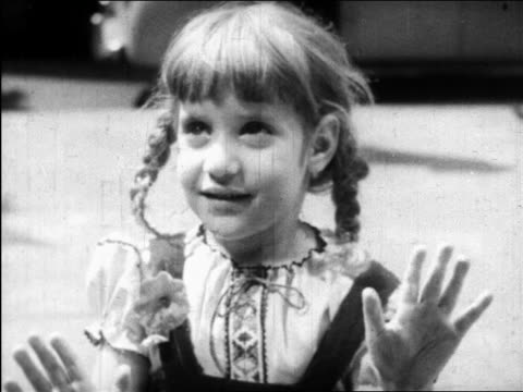 vidéos et rushes de b/w 1945 close up little girl with braids at window looking up + smiling / nyc / educational - une seule petite fille