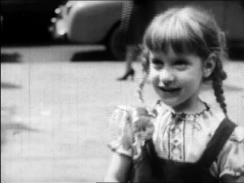 vidéos et rushes de b/w 1945 close up little girl with braids looking up on new york city street / educational - une seule petite fille