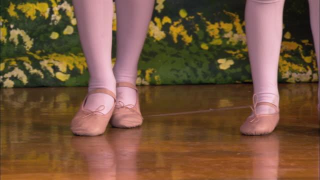 Close up little girls' feet dancing in ballet shoes