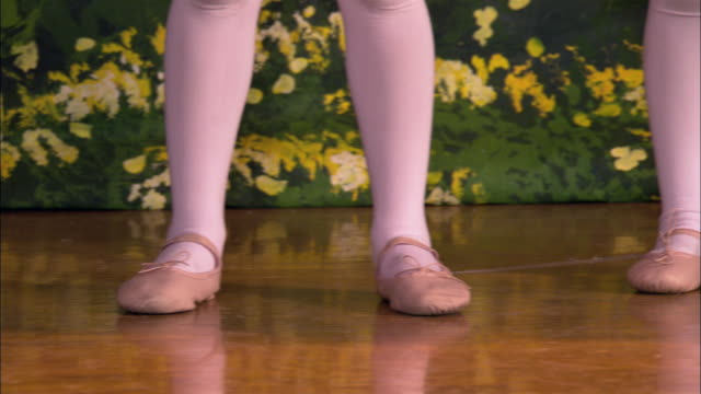 Close up little girls' feet in ballet shoes / tilt up medium shot girls dancing on stage