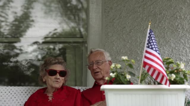 close up local residents lowell and betty tripp who have been married for 73 years wait for the beginning of the 4th of july parade at their front... - lowell stock videos & royalty-free footage