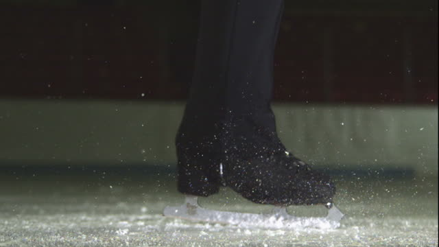 close up, locked down - a figure skater spins on the ice / usa - ghiacciato video stock e b–roll