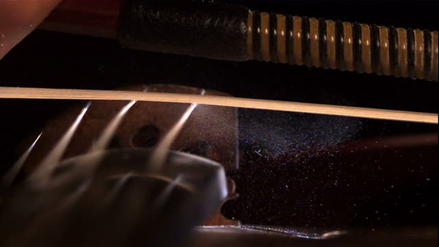 close up, locked down - a hand draws a bow across the strings of a violin / usa - violin stock videos & royalty-free footage