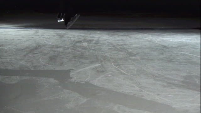 close up, locked down - a skater lands on ice / usa - アイススケート場点の映像素材/bロール
