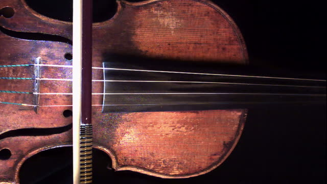 close up, locked down - a violin bow draws across the strings of a violin / usa - violin stock videos & royalty-free footage