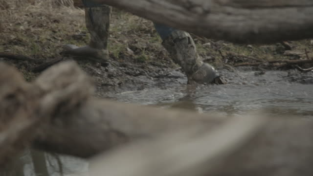 close up looking through logs in a stream featuring a hunter's boots splashing through the steam and mud. - stiefel stock-videos und b-roll-filmmaterial