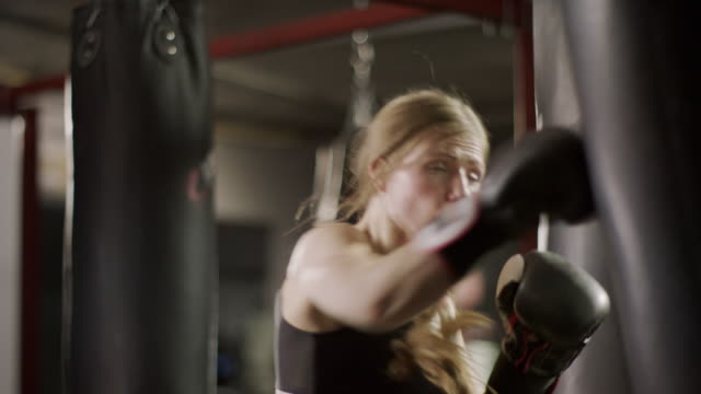 close up low angle panning shot of female boxer hitting heavy bag / lehi, utah, united states - punch bag stock videos & royalty-free footage