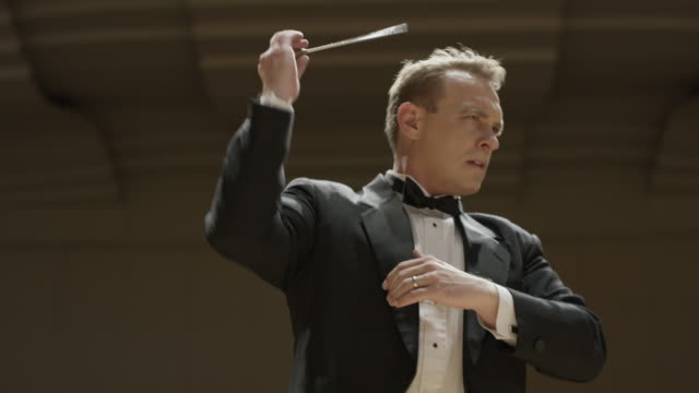 Close up low angle panning shot of orchestra conductor / Salt Lake City, Utah, United States