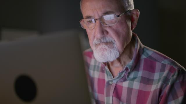 vídeos de stock e filmes b-roll de close up low angle shot of older man using laptop / cedar hills, utah, united states - idoso na internet