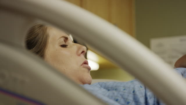Close up low angle shot of pregnant woman laying in hospital bed / Midvale, Utah, United States