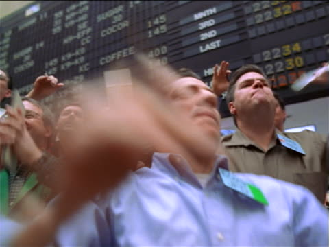 close up low angle PAN traders shaking arms + shouting on floor of Coffee, Sugar + Cocoa Exchange / NYC