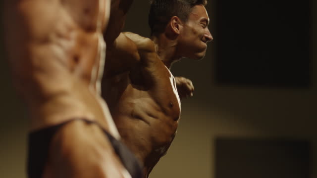 close up low angle view of bodybuilders posing on stage at competition / draper, utah, united states - culturismo video stock e b–roll