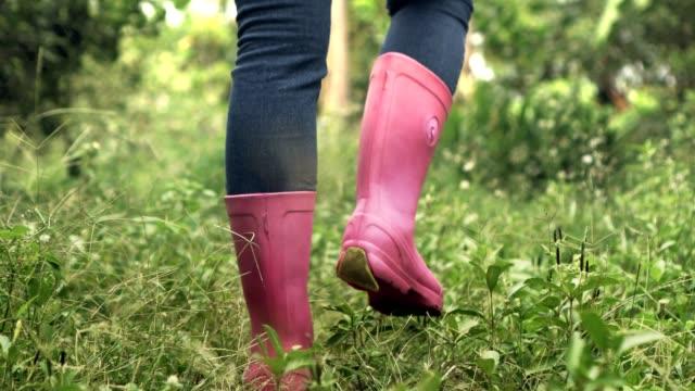 close up low shot pink shoe boot woman farmer walking in green grass