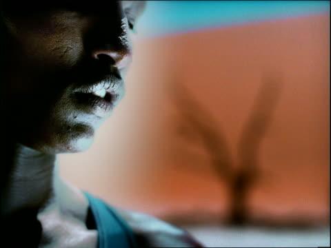 stockvideo's en b-roll-footage met overexposed close up lower half of black man's face looking down in desert / namibia, africa - menselijke neus