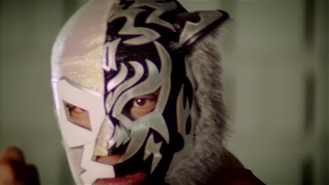 Close up luchador 'Black Tiger'/ zoom out medium shot posing with flexed bicep/ Monterrey, Mexico